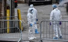 FILE: Medical workers remove a body from a refrigerated truck outside of the Brooklyn Hospital on 31 March 2020 in New York City. Due to a surge in deaths caused by the coronavirus, hospitals are using refrigerated trucks to makeshift morgues. Picture: AFP.