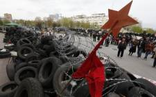 Pro-Russian protesters stand in front of a barricade in front of an occupied building of the Regional State Administration in Donetsk on 20 April. Picture: AFP.