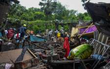 National Disaster Response Force (NDRF) and other rescue team personnel inspect the site of the landslide in a slum area where 23 people were killed after several homes were crushed by a collapsed wall and a landslide triggered by heavy monsoon rains in Mumbai on 18 July 2021. Picture: Sujit Jaiswal / AFP