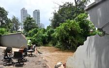 A man looks at the Krukut river where an embankment broke through the wall, flooding the area in Kemang in Jakarta on February 21, 2021, a day after parts of Indonesia's capital were inundated with flooding from seasonal heavy rains. Picture: Adek Berry / AFP.