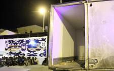 Men from African countries sit in Tripoli on 5 June 2017 next to a truck which was used to carry illegal migrants in the area of the coastal town of Guarabouli. Picture: AFP.