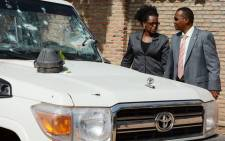 Burundian investigators stand next to the shrapnel-riddled vehicle in which Tutsi General and security advisor to Burundi's vice president Athanase Kararuza was killed on 25 April 2016 in Bujumbura. Picture: Onesphore Nibigira/AFP.