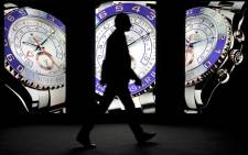 FILE. A visitor walks past an advert at the booth of the Swiss watchmaker Rolex at the Baselworld fair in Basel. Picture: AFP.