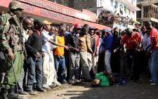 A man falls on the ground after viewing the scene of an explosion on the outskirts of Nairobi's business district on 16 May 2014. Picture: AFP.