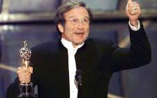 Robin Williams holds up his Oscar after winning in the best actor in a supporting role category in 1998 for his role as a psychotherapist helping a troubled maths genius in 'Good Will Hunting'. Picture: AFP.