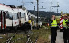 Rescuers stand on the site of a train accident on July 29, 2013 in Granges-pres-Marnand, western Switzerland. Two trains collided head-on, injuring 40 passengers, at least five of them seriously, police said. Picture: AFP