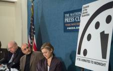 """Thomas Pickering, Sivan Kartha, member of the Bulletin's Science and Security Board, and Sharon Squassoni, member of the Bulletin's Science and Security Board sit by by the """"Doomsday Clock"""" showing that the world is now three minutes away from catastrophe. Picture: AFP"""