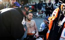 An Israeli man is treated by medics after he was stabbed by a Palestinian who wounded him during a stabbing rampage on a Tel Aviv bus on 21 January 21, 2015. The Palestinian was shot by a passing prison officer. Picture: AFP