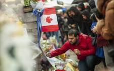 FILE: In this file photo taken on24  April 2018 a man writes a message at a memorial near the site of the deadly van attack in Toronto, Ontario. Picture: AFP.
