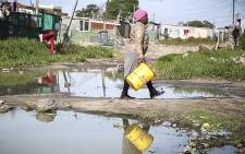 A woman cross a flooded road on a makeshift bridge in Sweet Home Farm, an informal settlement in Philippi, Cape Town, after some heavy rains in the week. Picture: Thomas Holder/EWN