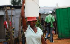 FILE: A resident collects water in an informal settlement in Rabie Ridge. Picture: EWN