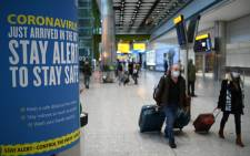 Coronavirus health warnings are seen in the arrivals hall at London Heathrow Airport in west London, on 15 January 2021. Picture: DANIEL LEAL-OLIVAS/AFP