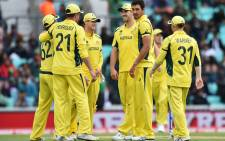 Australia cricketers celebrate the fall of a wicket. Picture: AFP