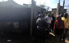Bekkersdal community members congregate at the shack where three children were killed during a fire on 29 May 2018. Picture: Thando Kubheka/EWN