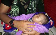 This handout picture taken and released by the Indonesian Military on 17 March 2019 shows a soldier cradling a rescued five-month-old baby, who was trapped for hours under rubble following flash floods in Sentani. Picture: AFP