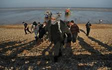 FILE: Migrants are escorted to be processed after being picked up by an RNLI (Royal National Lifeboat Institution) lifeboat while crossing the English channel at a beach in Dungeness, southeast England on 7 September 2021. Picture: AFP
