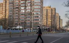 FILE: A man wearing a protective mask walks along an empty street in Beijing on 31 January 2020, following a SARS-like virus outbreak which began in the Chinese city of Wuhan. Picture: AFP