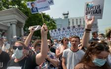 """A woman carries a placard reading """"Freedom for Furgal!"""", during an unauthorised rally in support of Sergei Furgal, the governor of the Khabarovsk region who was arrested a week ago, in the Russian far eastern city of Khabarovsk on 18 July 2020. Picture: AFP"""