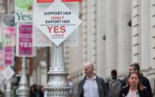 People walk past street lamps covered in placards from the 'Yes' and 'No' campaigns, urging people to vote in the referendum to repeal the eighth amendment of the Irish constitution, in Dublin on 24 May 2018. Picture: AFP.