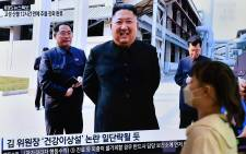 A woman walks past a television news screen showing a picture of North Korean leader Kim Jong Un attending a ceremony to mark the completion of Sunchon phosphatic fertiliser factory, at a railway station in Seoul on  2 May 2020. Picture: AFP