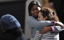 Two young women hug at a memorial service for the victims and relatives of the Sandy Hook Elementary School shooting on December 16, 2012. Picture: AFP
