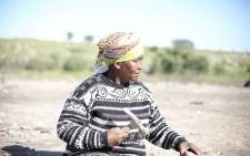 Olga janji, a 55 year old resident of Philippi, chips away at cement on used bricks that she will sell from the side of the road near her house in Philippi informal settlement, Cape Town. Picture: Andiswa Mkosi