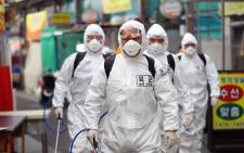 FILE: South Korean soldiers wearing protective gear spray disinfectant as part of preventive measures against the spread of the COVID-19 coronavirus, at a market in Daegu on 2 March 2020. Picture: AFP