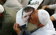 FILE: A supporter of the Muslim Brotherhood and Egypt's ousted president Mohamed Morsi kisses a poster of him as worshipers gather for prayer outside Cairo's Rabaa al-Adawiya mosque on 11 July, 2013. Picture:AFP