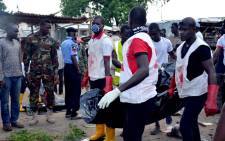 Nigerian Red-Cross workers carry a body away from the scene of an Improvised Explosive Device (IED) blast at Gomboru market in Maiduguri, 2015 detonated by a female suicide bomber who arrived on a taxi tricycle killings at least eight people and several other. Picture: AFP.