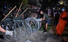 A monk watches soldiers as they try to install razor wire on the road in front of the Royal Thai Army headquarters in Bangkok on 14 October 2020 following a day of pro-democracy protests. Picture: AFP