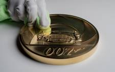 A handout picture released by the Royal Mint in London on 2 March 2020, shows Royal Mint designer Laura Clancy posing with a special edition James Bond themed seven kilogram Gold Proof coin, to celebrate the upcoming release of the 25th James Bond film. Picture: AFP
