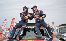 French driver Stephane Peterhansel (R) celebrates with teammates following his victory in the Dakar Rally in Saudi Arabia, on 15 January 2021. Picture: Franck Fife/AFP