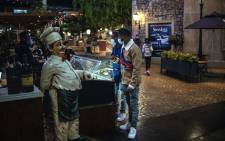 People check the menu of a restaurant at the Montecasino complex in Johannesburg, on July 3, 2020. The Italian themed leisure and casino complex has reopened its doors as South Africa has allowed casinos, cinemas and restaurants to resume their activity despite a rise in COVID-19 cases. Picture: AFP