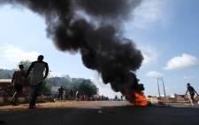 People walk past a fire on the road during clashes between youths in Abuja, Nigeria, on October 20, 2020, following the ongoing demonstrations against the unjustly brutality of SARS. Pic Kola Sulaimon / AFP