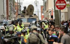 A Virginia State Police officer in riot gear keeps watch from the top of an armored vehicle after car plowed through a crowd of counter-demonstrators marching through the downtown shopping district 12 August 2017 in Charlottesville, Virginia. Picture: AFP.