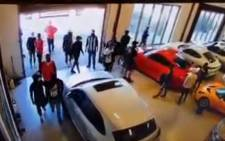 A YouTube screengrab of a group of men, some of them armed, walking into a car dealership in Brooklyn, Cape Town on 17 February 2021. Picture: YouTube