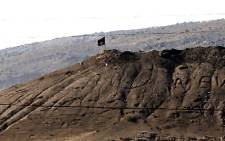 An Islamic State flag flies on a hill overlooking the Syrian town of Kobani, as seen from the border with Turkey in Suruc district, near Sanliurfa, Turkey on 7 October 2014. Picture: AFP.
