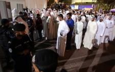 Kuwaiti mourners queue to be searched by security members outside the Sunni Grand Mosque on 27 June, 2015 as they arrive to give their condolences to the families of the victims of a suicide bombing which took place at the Shiite al-Imam al-Sadeq mosque the previous day, in Kuwait City. Picture: AFP.