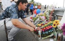 A woman lights a candle at a makeshift memorial outside Walmart, near the scene of a mass shooting which left at least 20 people dead, on 4 August 2019 in El Paso, Texas. Picture: AFP