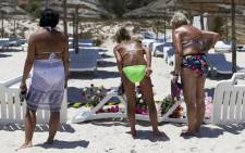 FILE. Tourists look at flowers at the site of a shooting attack on the beach in front of the Riu Imperial Marhaba Hotel in Port el Kantaoui, on the outskirts of Sousse south of the capital Tunis, on 27 June, 2015. Picture: AFP.