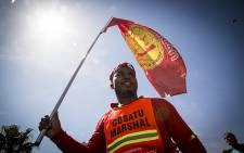 A Satawu flag wielding member of Cosatu marches to Parliament in Cape Town along with thousands others to hand over their demands. Picture: Thomas Holder/EWN