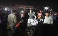 Pakistani rescuers use a stretcher to shift a body from a bomb blast site in Lahore on March 27, 2016. Picture: AFP.