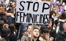 A person holds up a placard reading 'stop feminicide' during a protest at the International day for elimination of violence against women in Paris, on 23 November 2019. Picture: AFP.