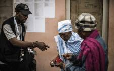 Elderly voters are directed by an Electoral Commission officials at a voting station in Bairo Popular in Luanda, on 23 August 2017. Picture: AFP.