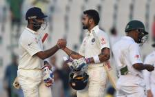 FILE: India's Cheteshwar Pujara, left, and captain Virat Kohli. Picture: AFP.