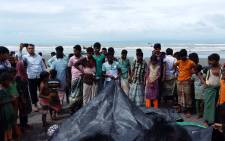 Bangladeshi onlookers watch as a man covers the bodies of Rohingya women and children on 31 August 2017 who drowned after their boat capsized. Picture: AFP