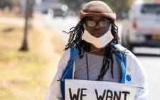FILE: Zimbabwean novelist Tsitsi Dangarembga holds a placard during an anti-corruption protest march along Borrowdale road, on 31 July 2020 in Harare. Picture: AFP