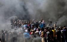 Palestinians chant slogans during clashes with Israeli security forces near the border between the Gaza Strip and Israel east of Gaza City on 14 May 2018. Picture: AFP
