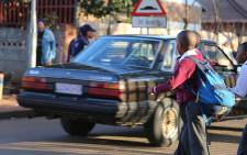 Roodepoort Primary pupils cross the road on their way to class as the school is reopened following weeks of closure. Picture: Reinart Toerien/EWN
