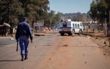 Police move to clear barricades and debris from the road in Sicelo informal settlement in Meyerton after service delivery protests on 18 June 2018.  Picture: Thomas Holder/EWN.